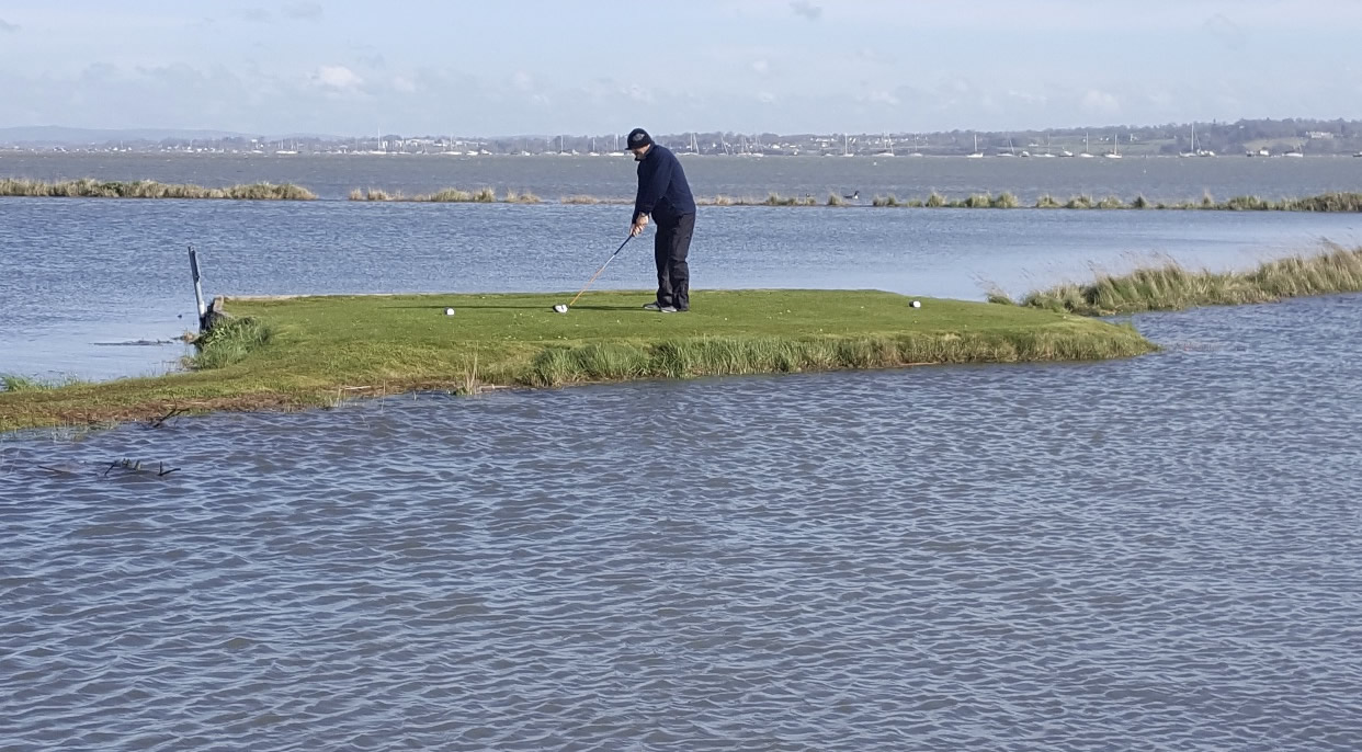 The white 18th tee with a high tide around it